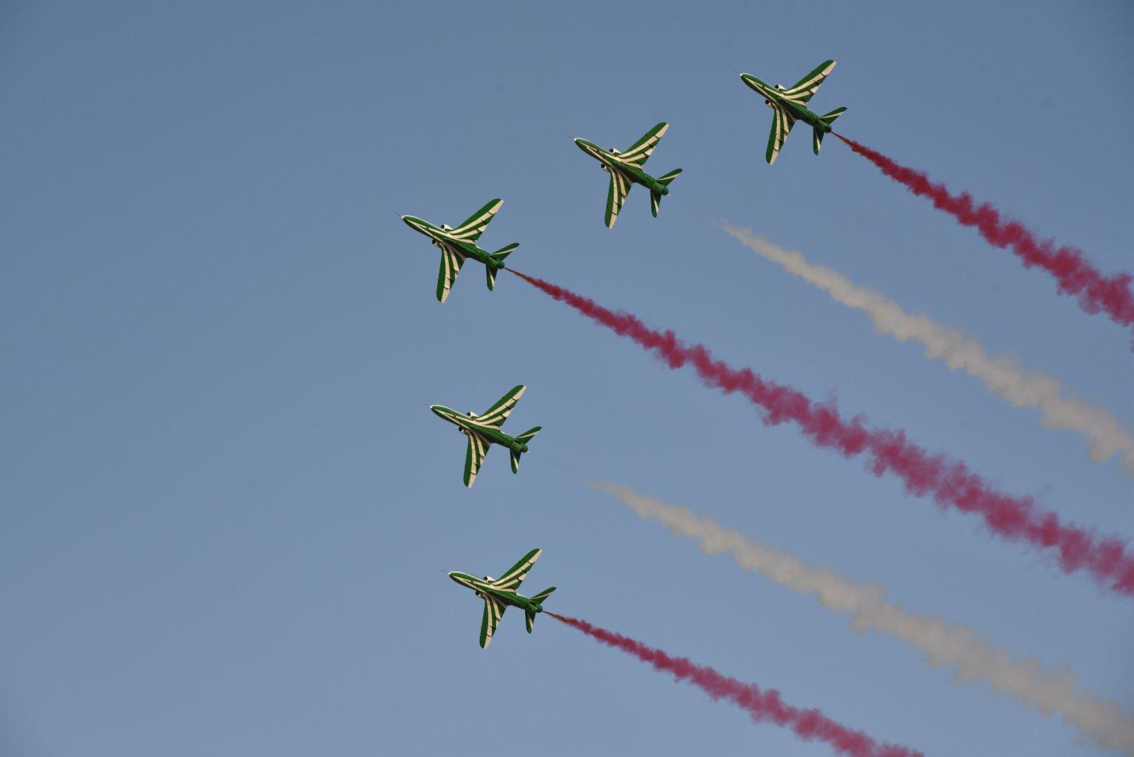 9月22日,在沙特阿拉伯首都利雅得,五架飛機在天空中噴射彩煙,並作出特技動作。(新華社)