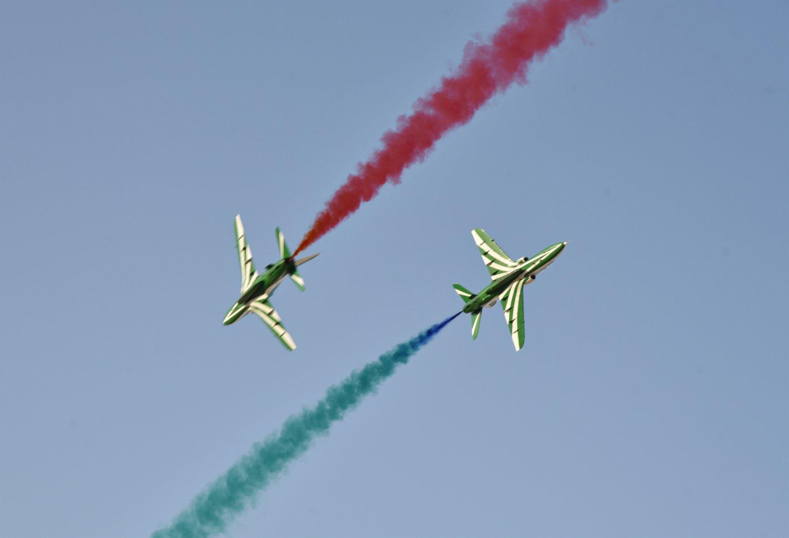 9月22日,在沙特阿拉伯首都利雅得,飛機在進行低空飛行並噴射彩煙。(新華社)