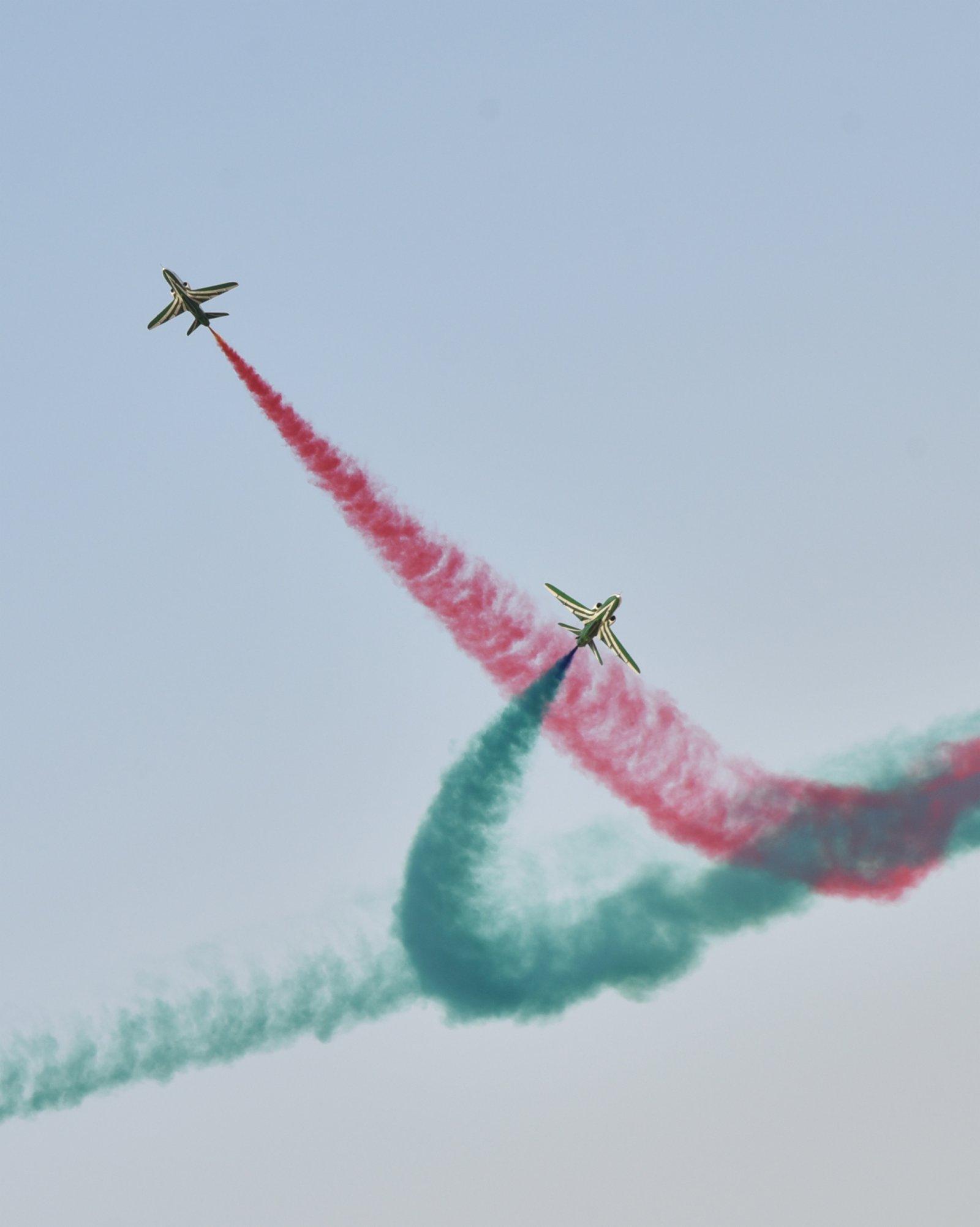 9月22日,在沙特阿拉伯首都利雅得,飛機在天空中噴射彩煙,並作出特技動作。(新華社)