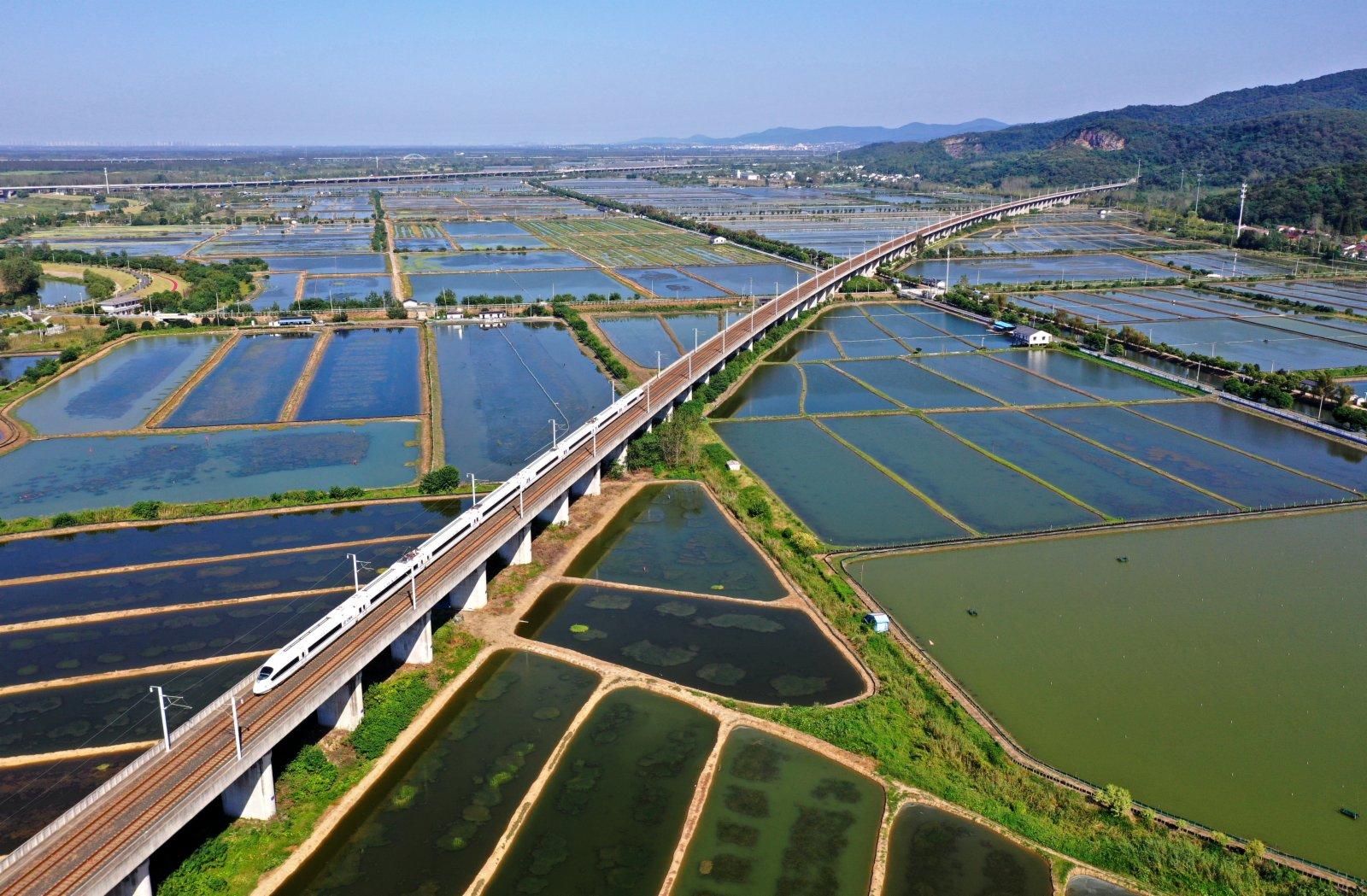 9月22日,列車從安徽省全椒縣十字鎮滁河圩區水產養殖基地上奔馳而過。(新華社)