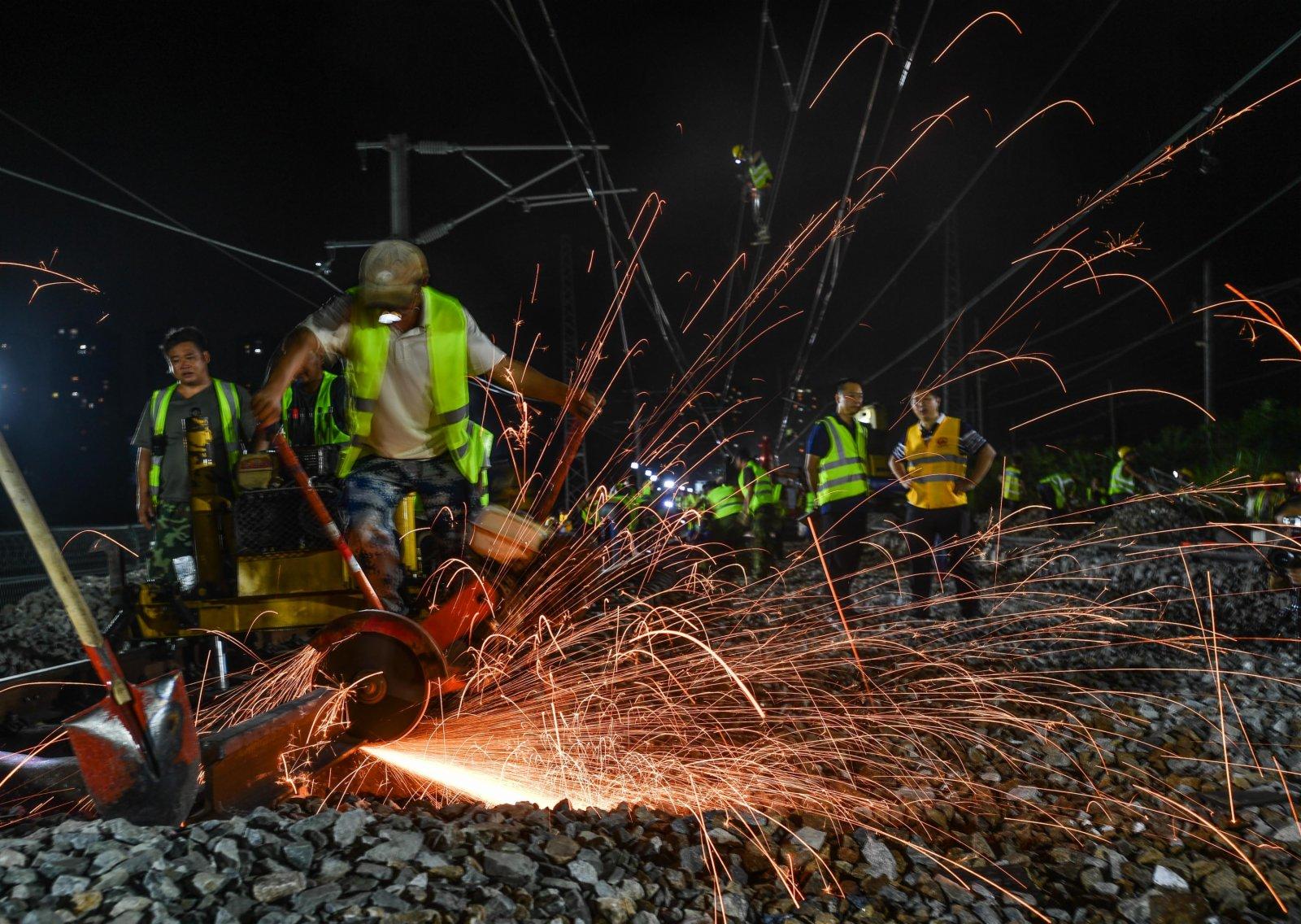 9月25日,施工人員在東莞塘廈贛深高鐵撥接廣深鐵路現場切割鋼軌。(新華社)