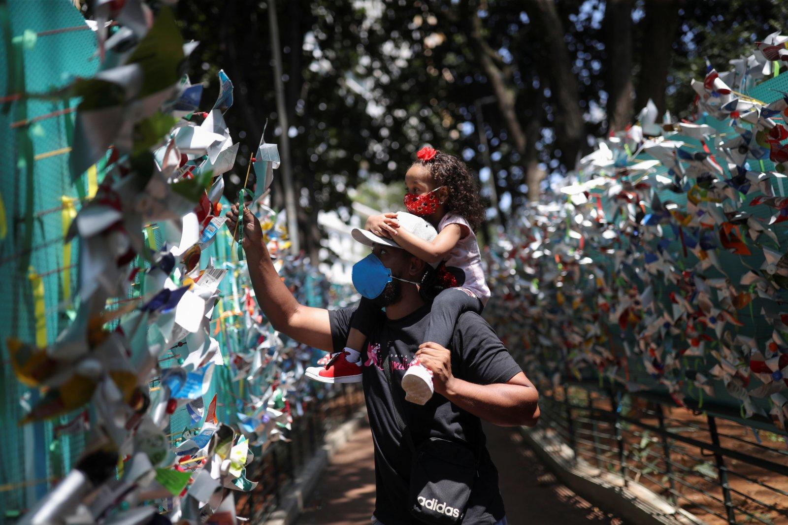 當地時間2021年10月6日,巴西聖保羅,人們在一條小路兩邊掛滿風車,悼念新冠肺炎逝者。(路透社)