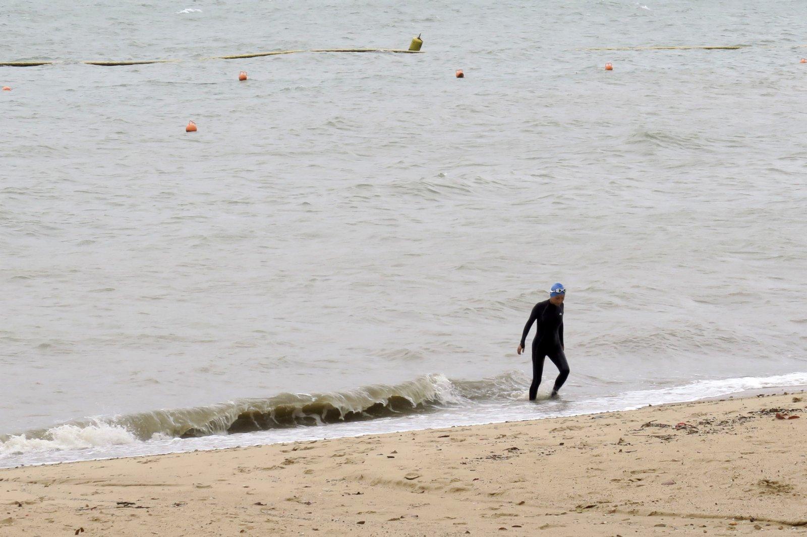 圖為有市民在八號風球下到屯門蝴蝶泳灘游泳。(中新社)