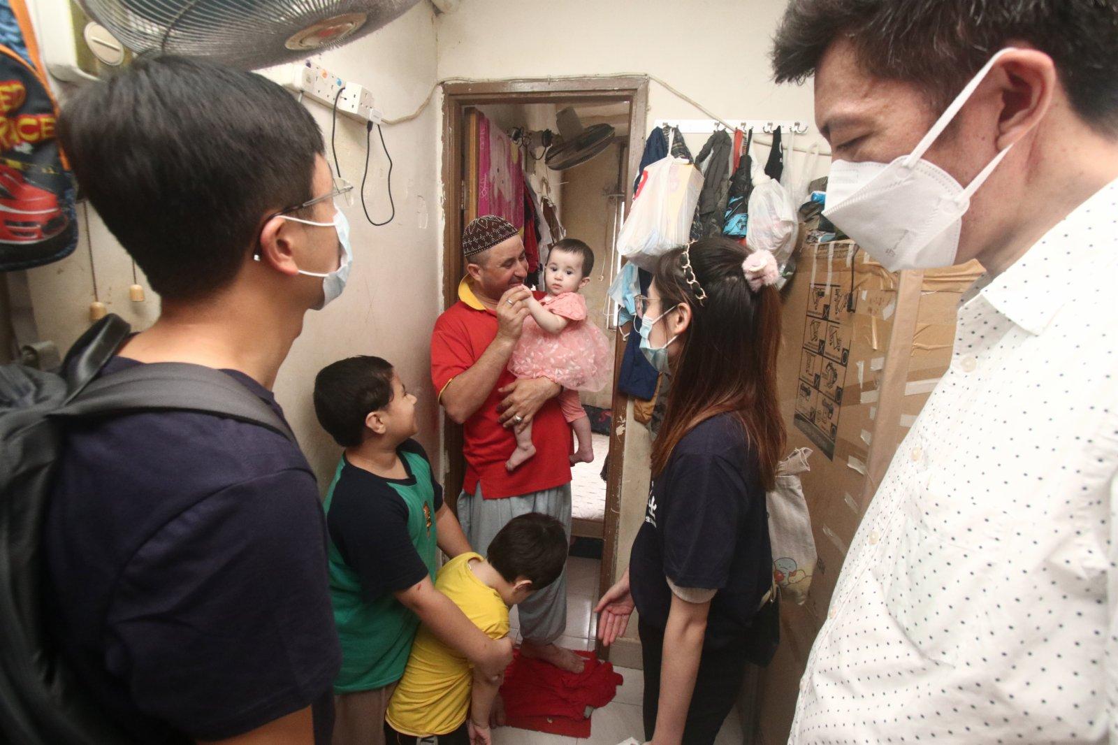 香港中文大學醫科畢業生李菀容、香港科技大學計算機科學四年級生林衍宏,在中聯辦教育科技部副部長徐凱的陪同下,探訪一個巴基斯坦裔的五人家庭。(香港文匯報記者 攝)