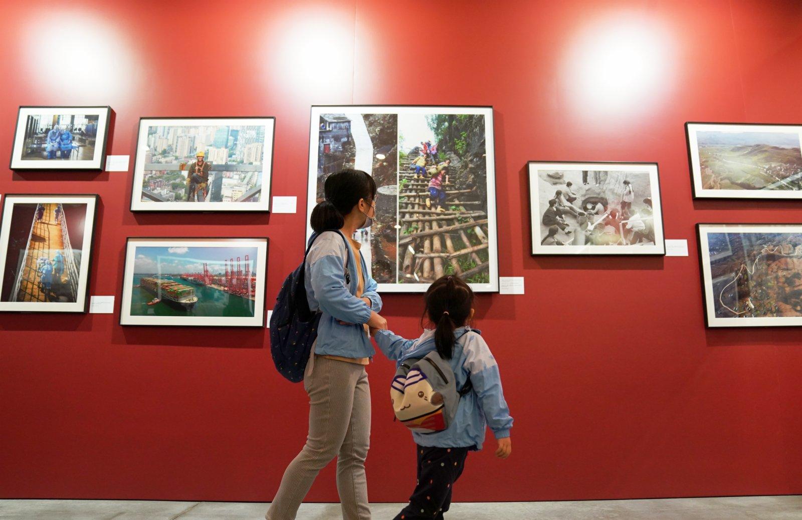 一名家長帶着孩子參觀展覽。(新華社)