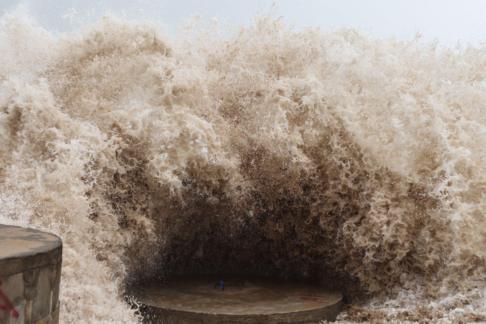10月13日,在萬寧市山根鎮的海邊,巨浪拍擊海岸。(新華社)